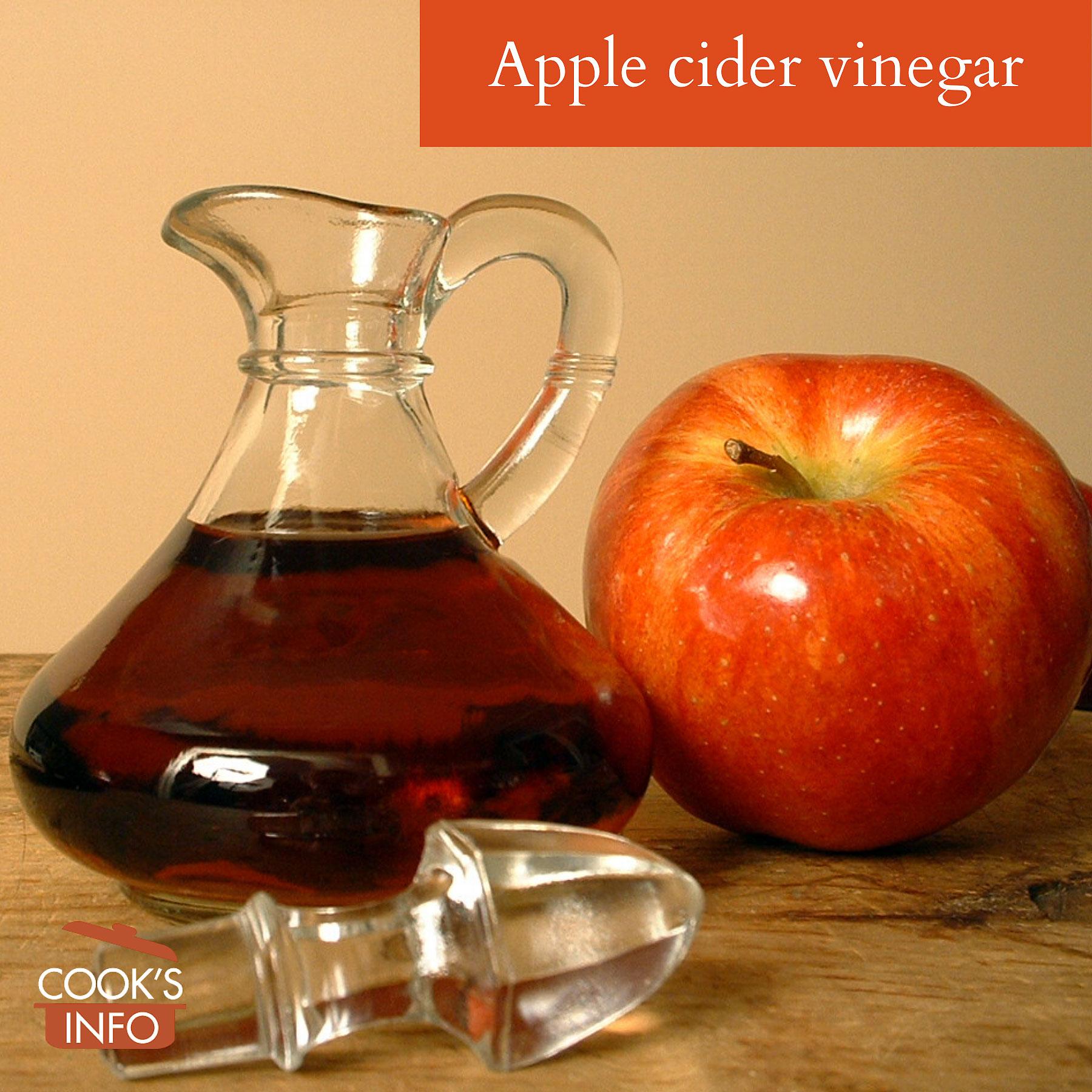 Apple cider vinegar next to an apple