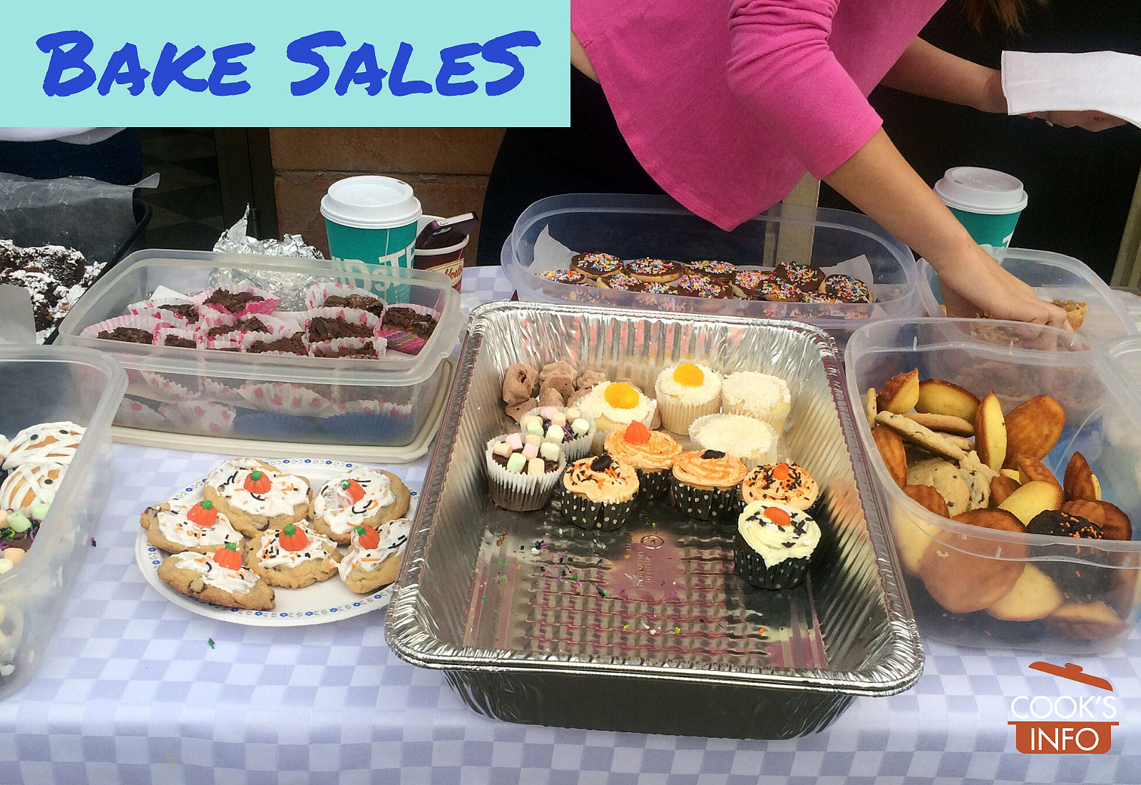 Photo of a table with baked goods for sale on it, woman arranging items