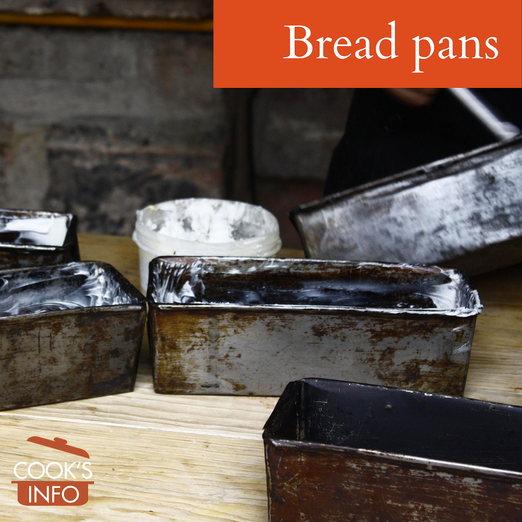 Bread pans being greased