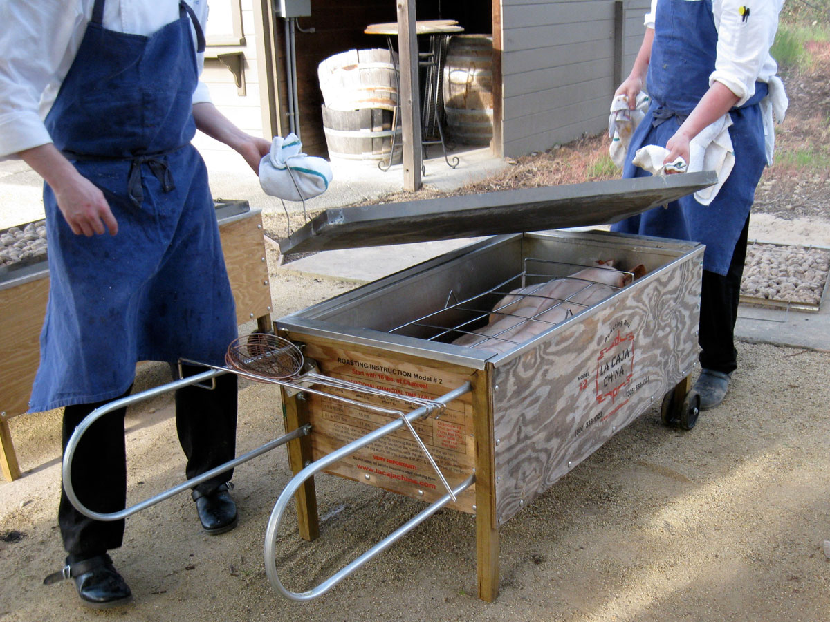 Pig being placed inside Caja China