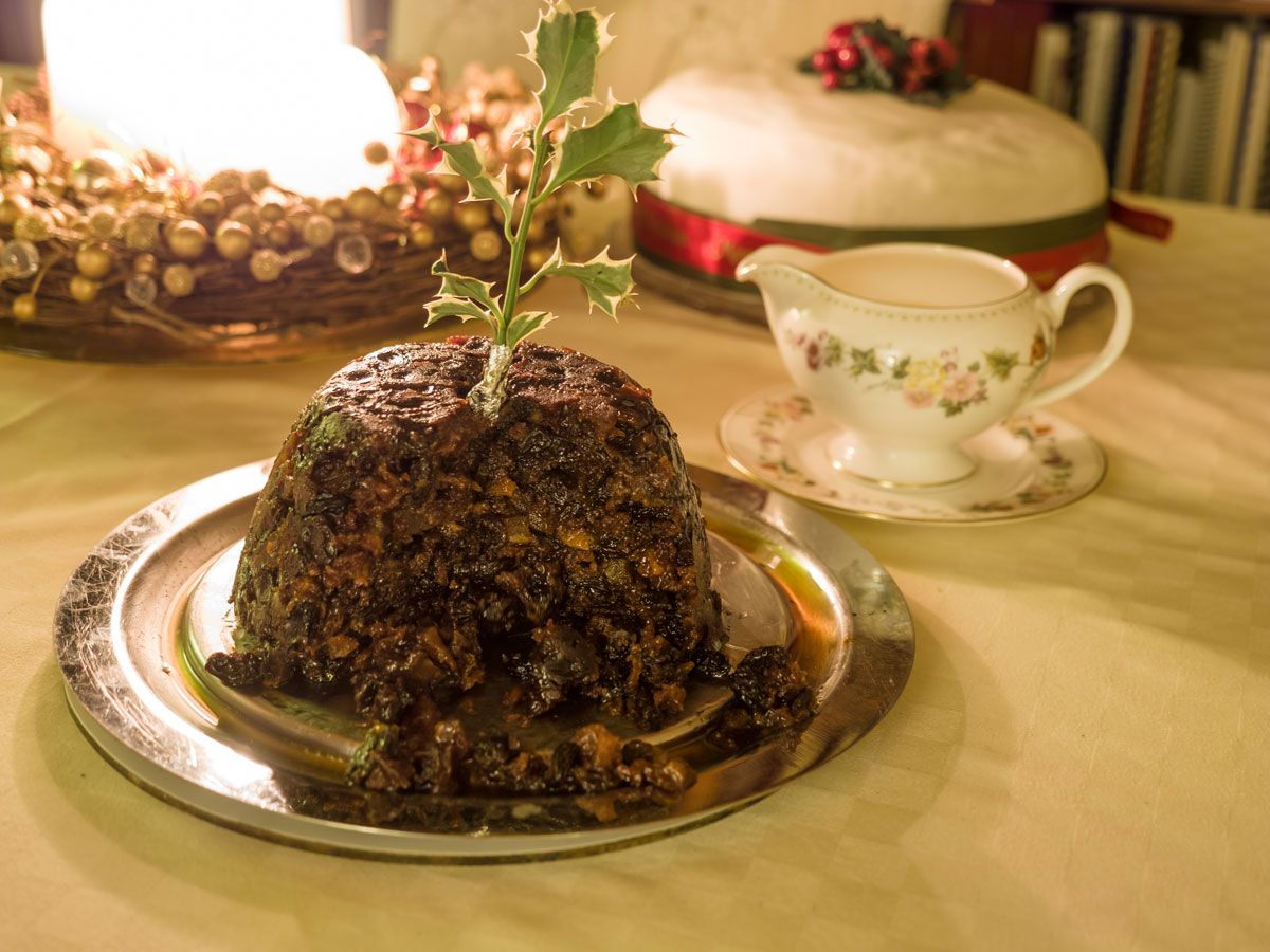 Christmas pudding with pitcher of cream