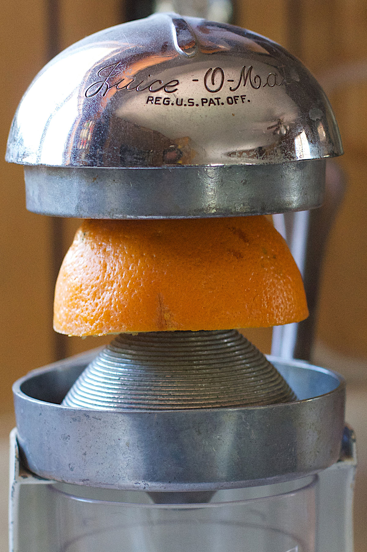 Manual hand-press citrus juicer in use