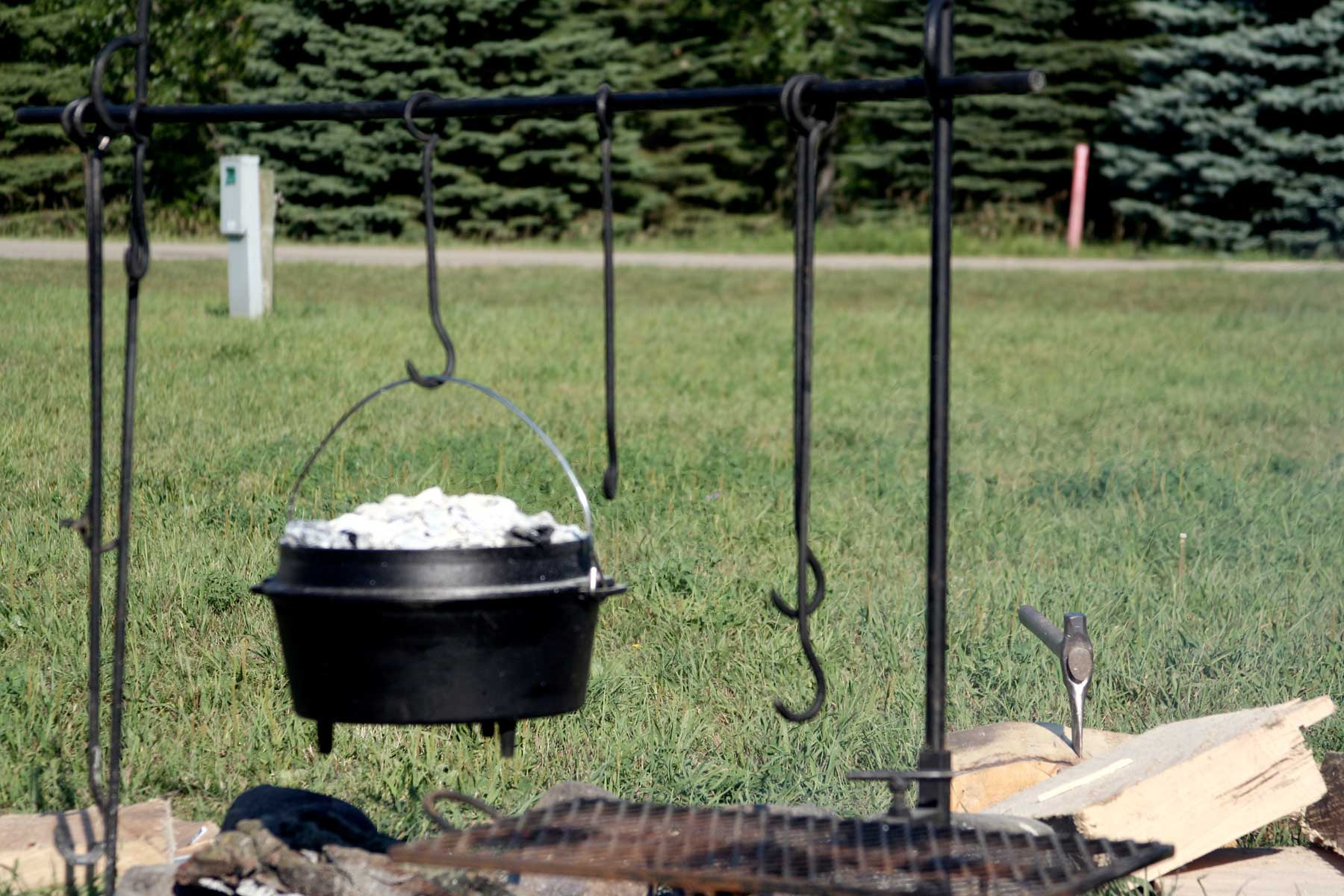 Dutch oven suspended by bail handle over fire
