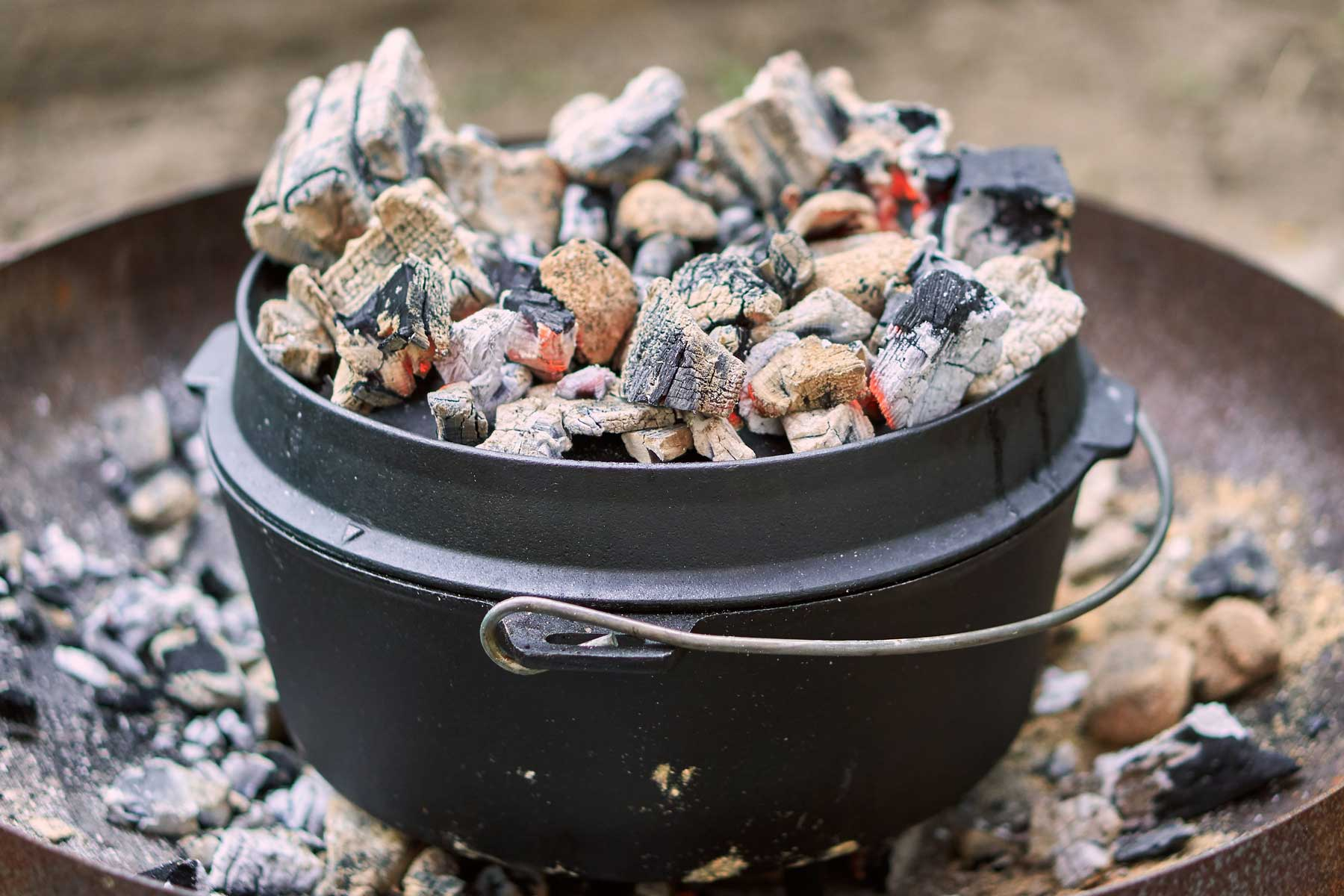 Dutch oven with coals on lid.