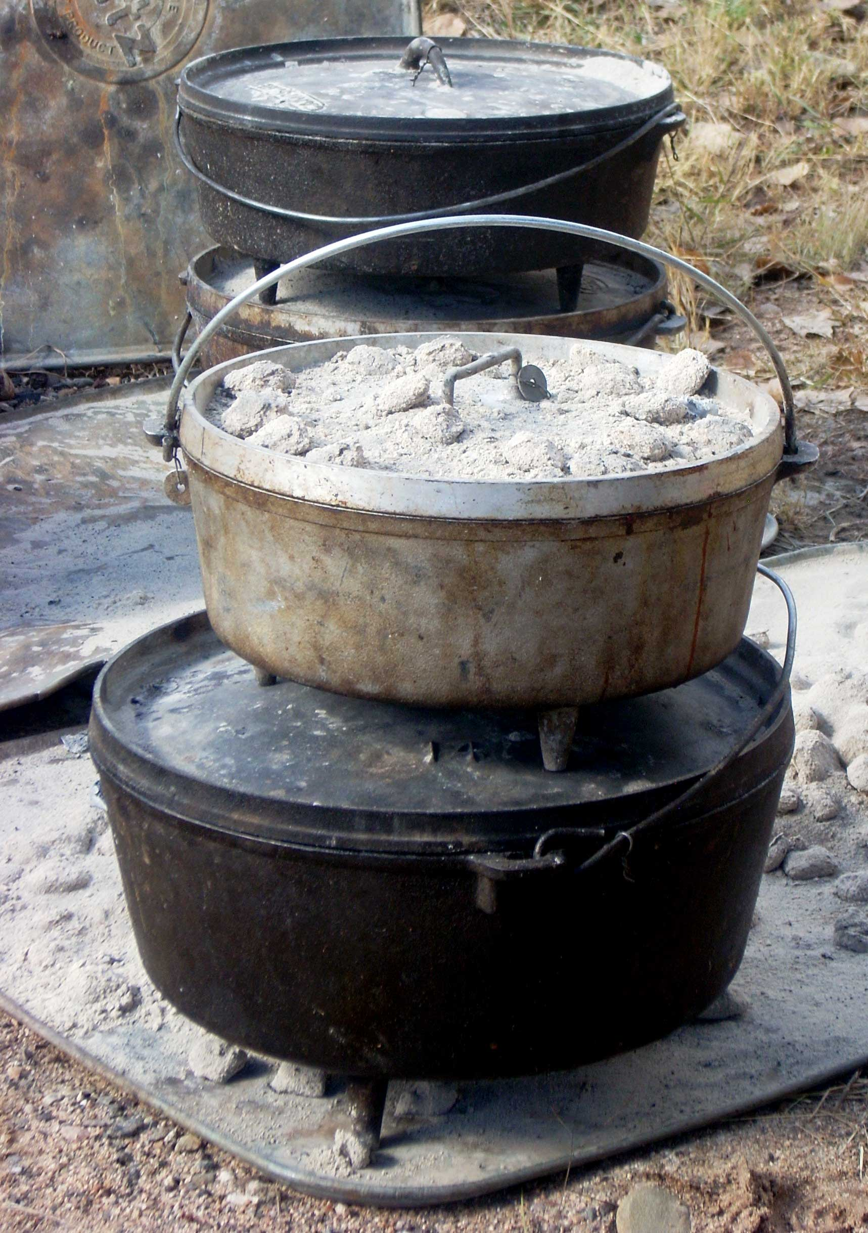 Campfire Dutch ovens showing ashes on top of lid