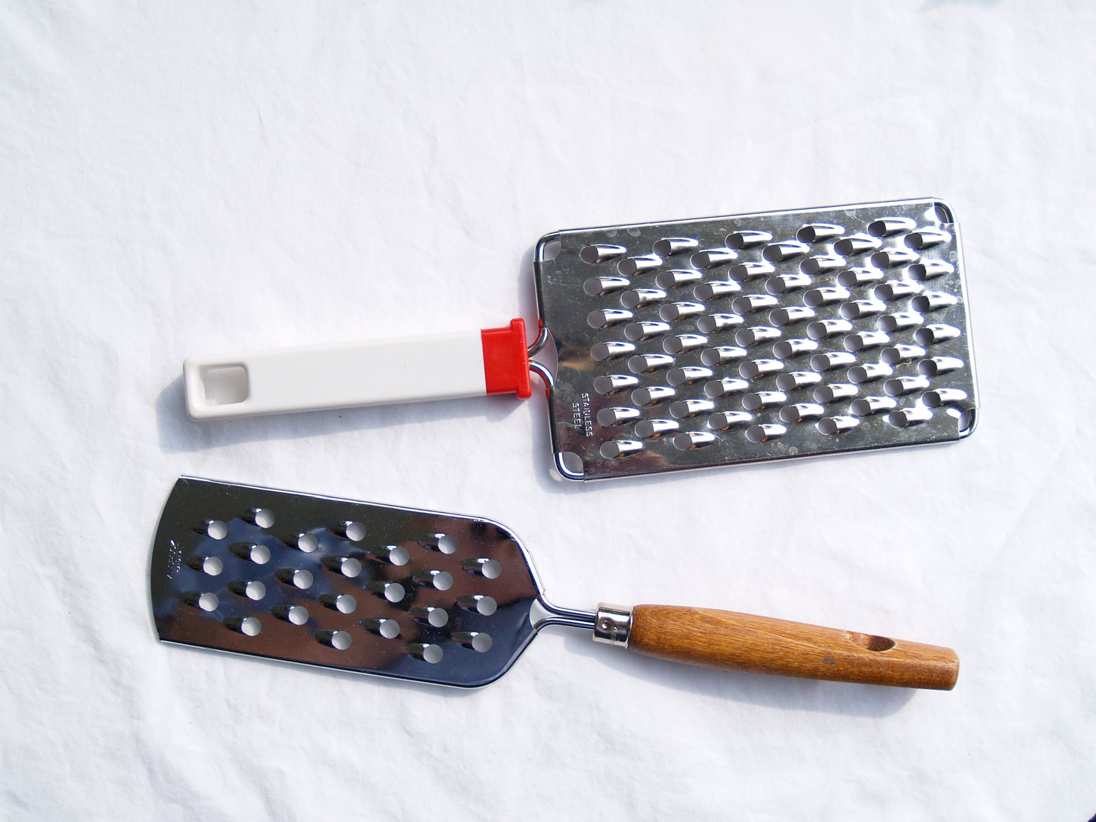 Hand-held flat graters