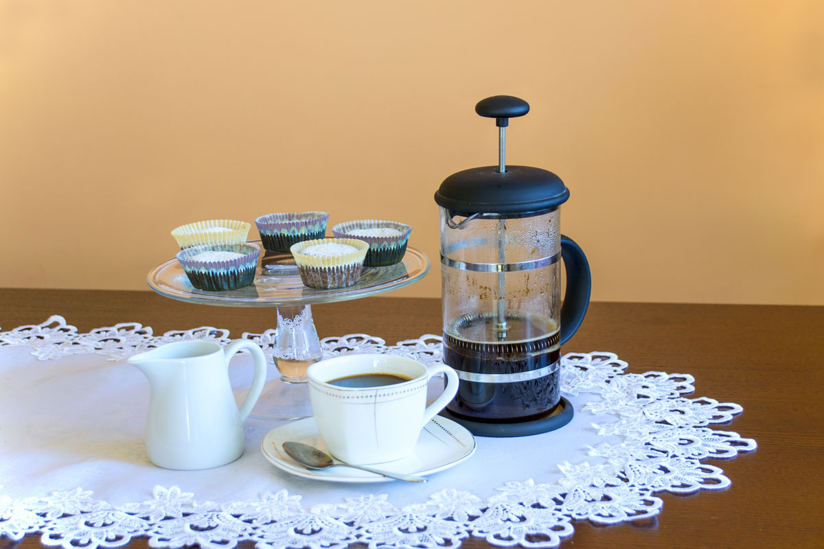 French press coffee maker with pastries