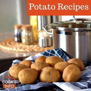 Unpeeled potatoes next to a pot