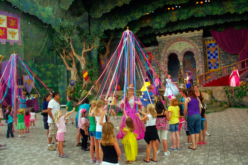 Children learning to dance around maypole