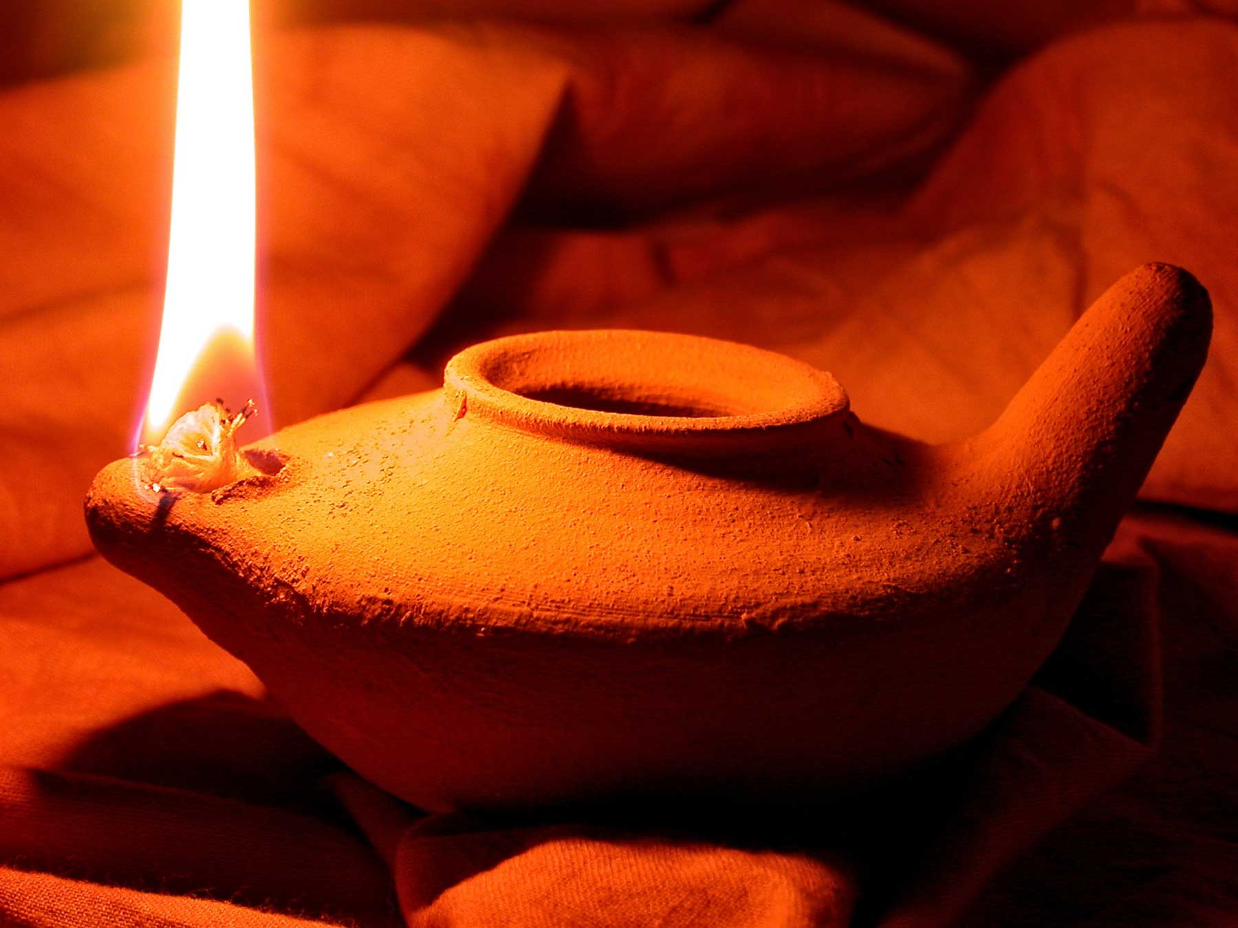 Clay olive oil lamp alight