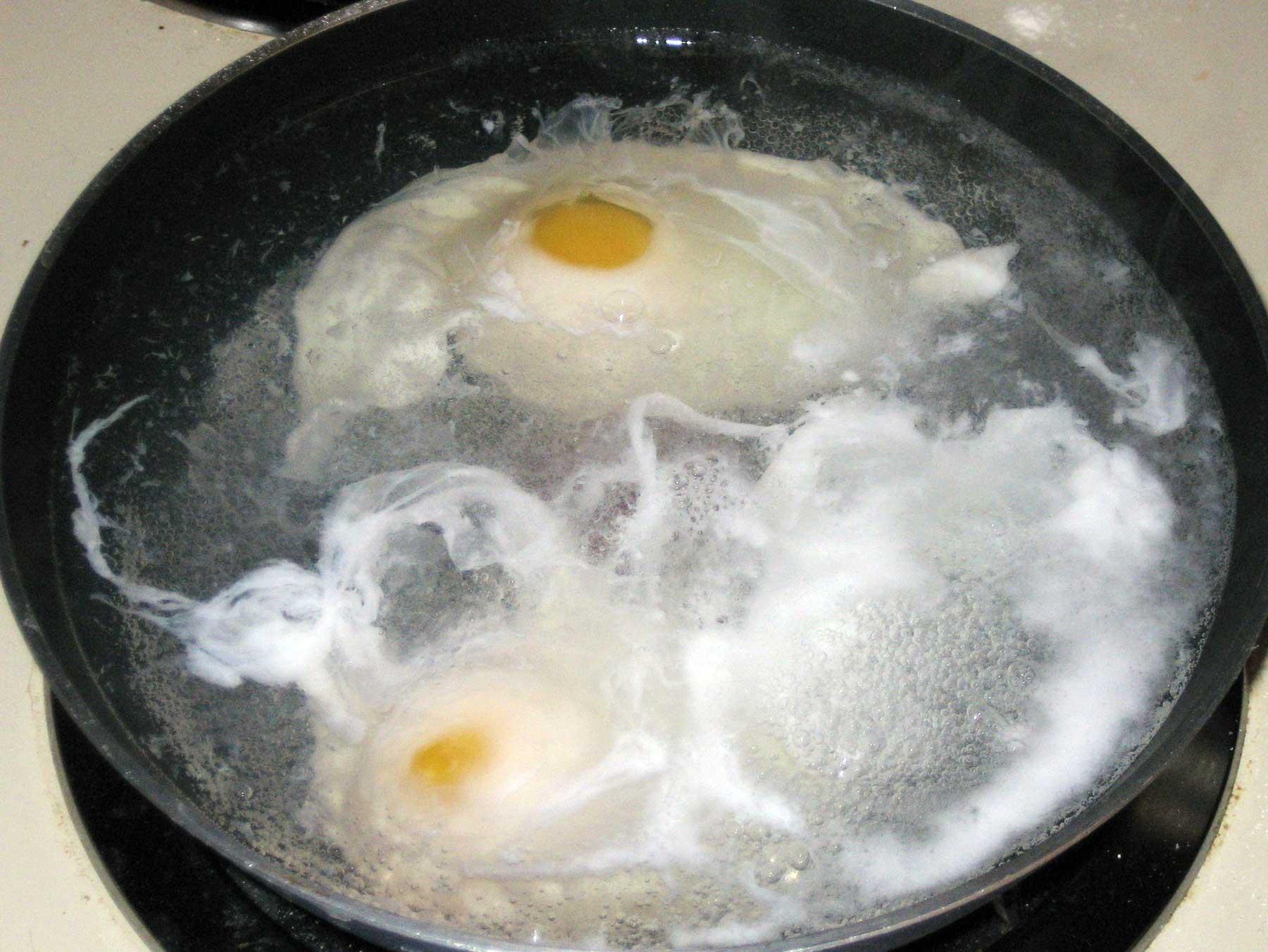 Eggs poaching in a pan of water