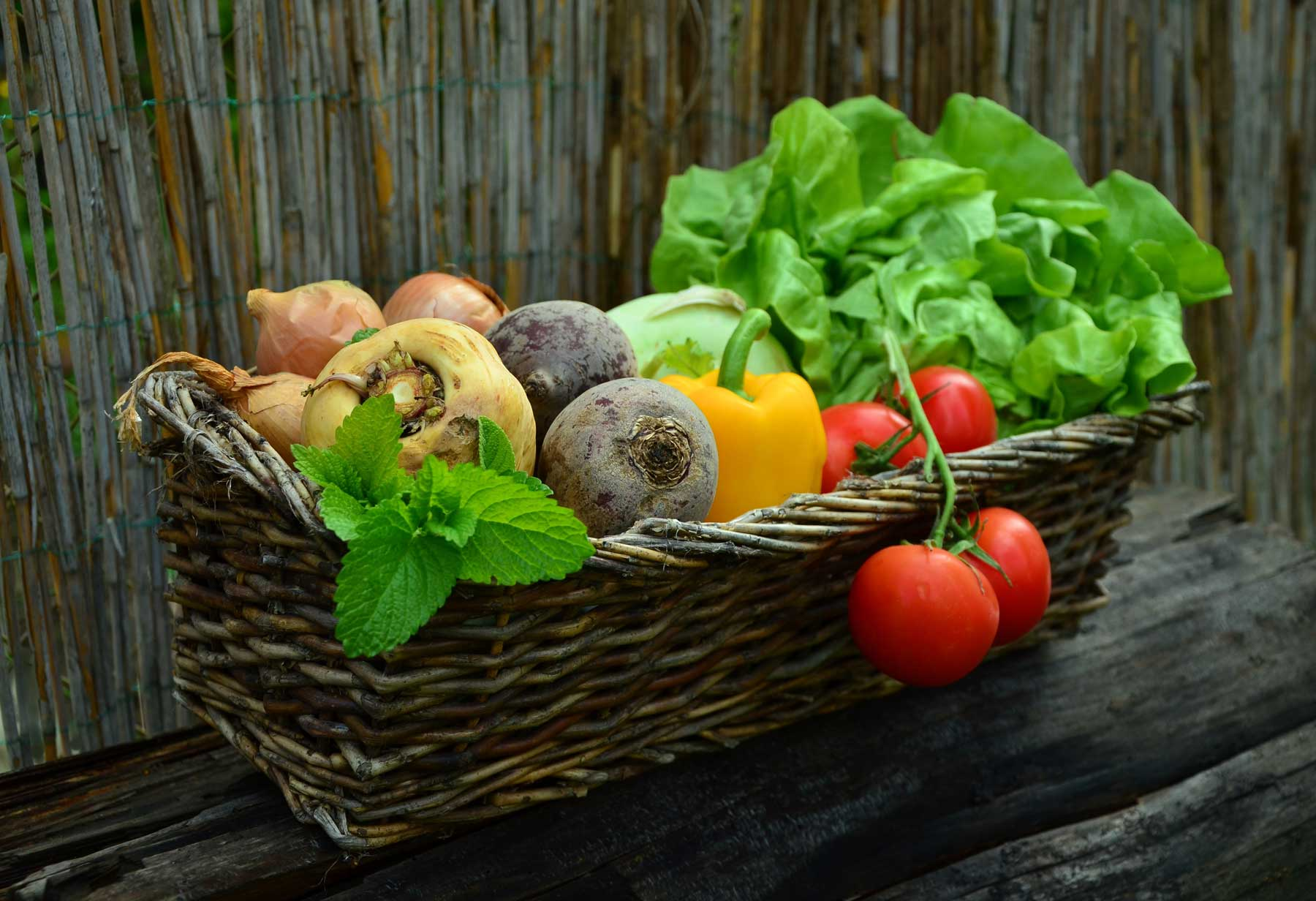Assortment of vegetable types in basket. Root, fruiting, and leafy veg